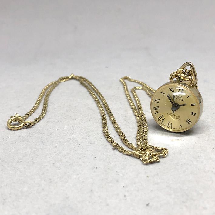 นาฬิกาห้อยคอ BULER 1970 ระบบไขลาน ตัวเรือนเป็นลูกแก้วกลมใส มองเห็นหน้าปัดสีเหลืองทอง เดินเวลา 3 เข็ม