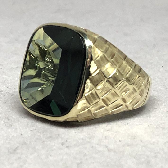 แหวนทองคำงานนอก ด้านหน้าประดับพลอยเขียวเนื้ออ่อนเจียรไนหลบใน สำหรับแฟรแสงสะท้อนใน หน้าตัดเรียบแบน ด้
