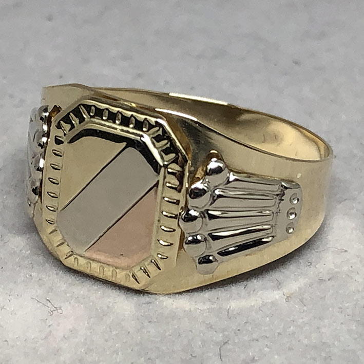 แหวนทองคำงานนอก ด้านหน้าแสดงสัญลักษณ์ทอง 3 สี  หน้าตัดเรียบแบน ด้านข้างแสดงแสดงตรามงกุฏ ตัวเรือนทอง